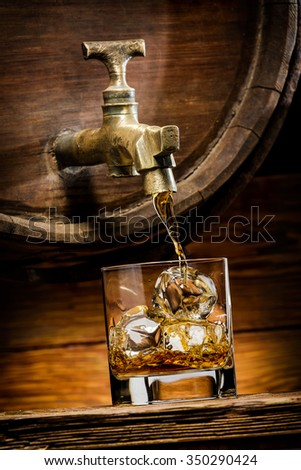 whiskey or brandy is poured into a glass from oak barrel - stock photo