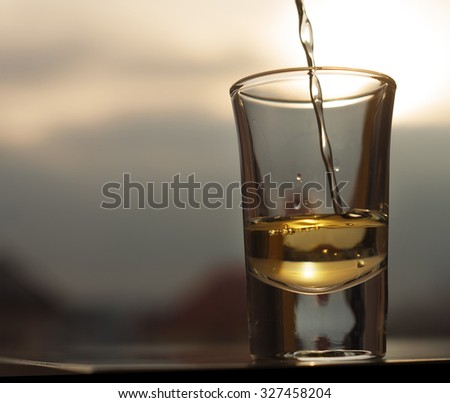 Whiskey pouring into shot glass - stock photo