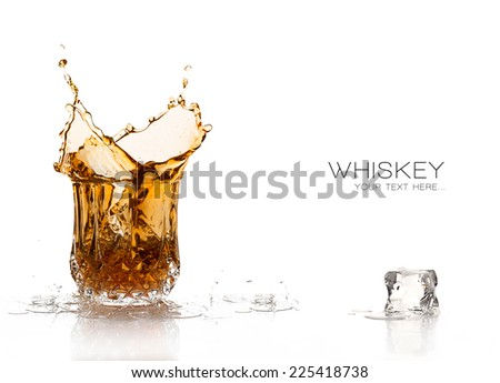 Whiskey splash on elegant glass of cut glass and one ice cube melting in foreground. Still life isolated on white background with sample text - stock photo