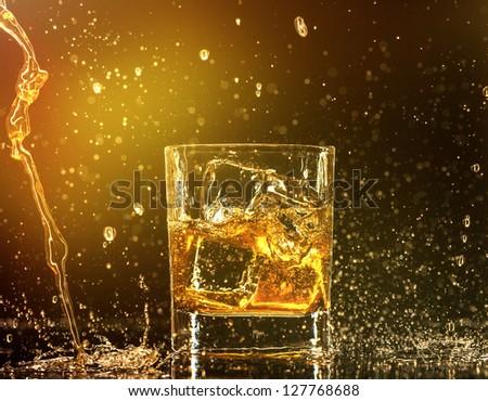 Whiskey splashing around glass - stock photo