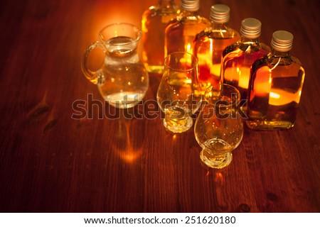 Whiskey tasting: sample bottles, glencairn glasses and a jug of water - stock photo