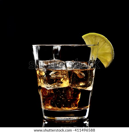 Whiskey with ice in glass isolated on black background  - stock photo