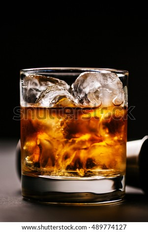 Whiskey with ice in rocks glass on black background