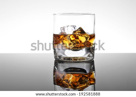 Whiskey with ice in simple glass - stock photo