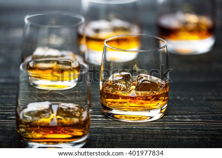 whiskey with ice on a black wooden background,selective focus - stock photo