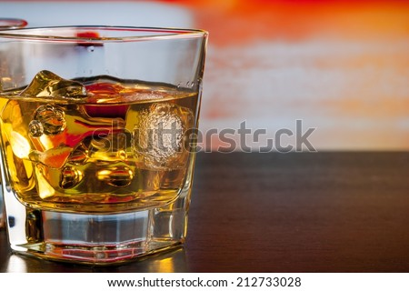 whiskey with ice on bar table lounge bar atmosphere with space for text - stock photo