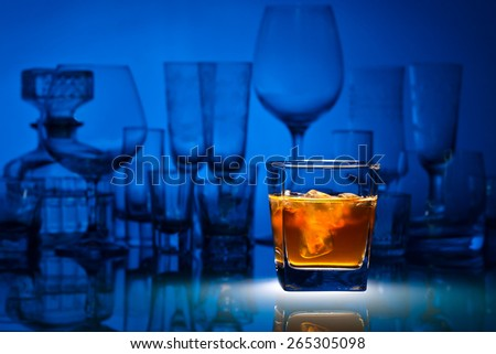 whiskey with ice on glass table in bar - stock photo