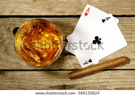 whiskey with playing cards and cigar on old wooden surface - stock photo