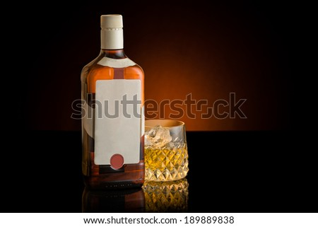 Whisky bottle and glass with copy space. White blank label. Orange Background. Whiskey. - stock photo
