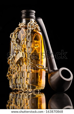 whisky bottle and pipe - stock photo