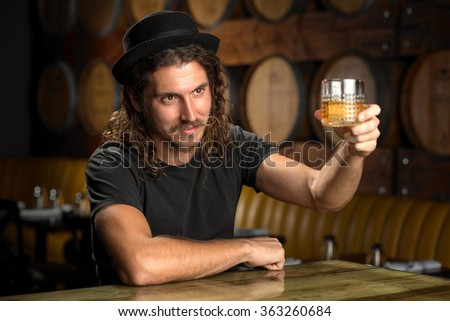 Whisky glass cheers stylish man drinking bourbon at a whiskey distillery restaurant bar  - stock photo