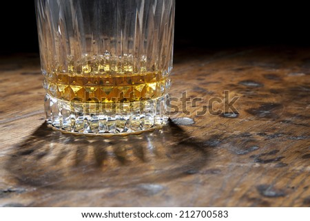 Whisky glass on an old wooden table