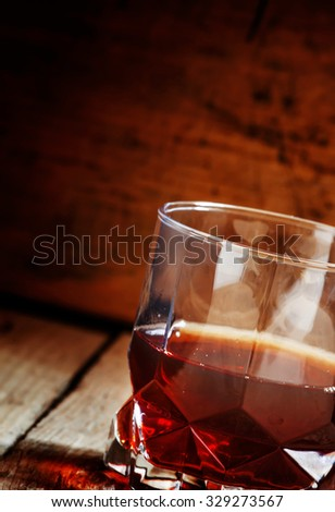 Whisky in a glass on old wooden dark background, selective focus