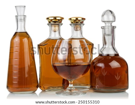 Whisky in bottles and glass isolated on white - stock photo