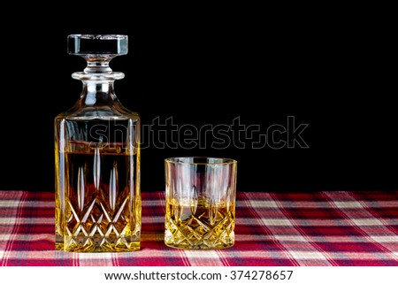 Whisky on tartan table cloth against a black background