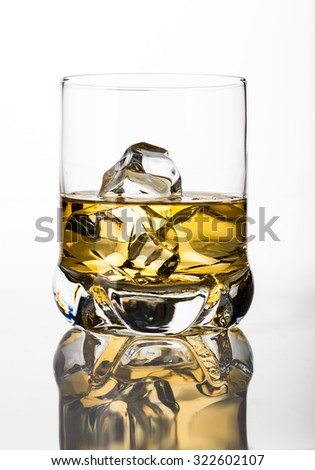 Whisky on the rocks on white background with reflection