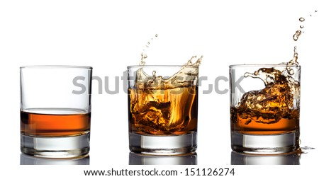 Whisky splashing out of glass on a white - stock photo