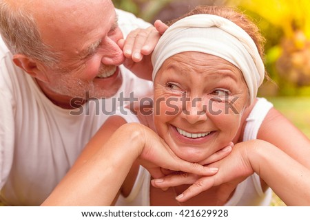 whispering smiling older couple - stock photo