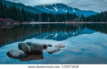Whistler mountain reflected in lost lake with a blue hue. - stock photo