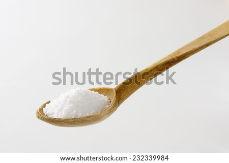 whit of coarse grained salt on the old wooden spoon - stock photo