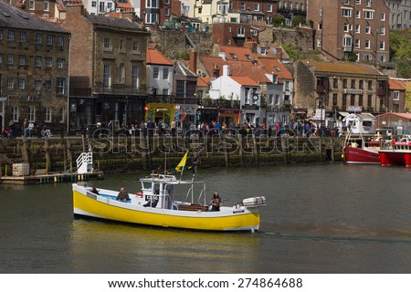 WHITBY, ENGLAND - April 25, 2015:  A Yellow Boat in Whitby Harbor. Whitby is a Seaside Town, Port and Civil Parish in the Borough of Scarborough and English County of North Yorkshire.