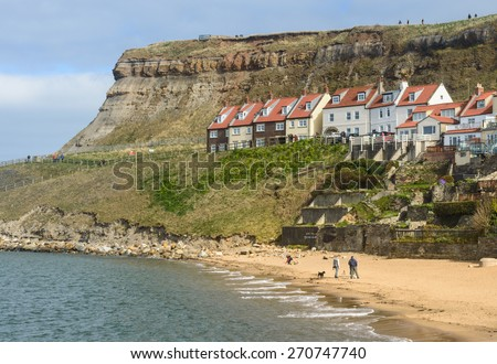 WHITBY, ENGLAND - APRIL 18: Groups of people, and a dog, enjoying the sun on the beach, in Whitby, North Yorkshire, England. On 18th April 2015. - stock photo