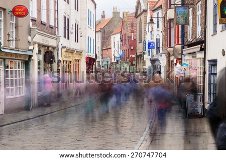 WHITBY, ENGLAND - APRIL 18: People shopping on Church Street, slow motion blur used, in Whitby, North Yorkshire, England. On 18th April 2015.