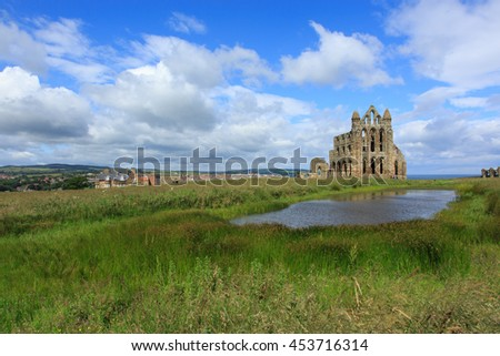 Whitby, England - 8 July, 2016: Whitby Abbey is a ruined Benedictine Abbey that was the inspiration for the Dracula novel.  It sits high on a cliff overlooking the fishing port of Whitby.