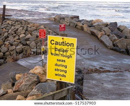 WHITBY, ENGLAND - NOVEMBER 5: Sign warning of rough seas on East Pier. In Whitby, North Yorkshire, England. On 5th November 2016.