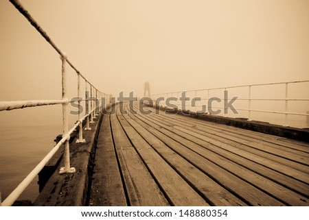 Whitby pier with fog in the background - stock photo