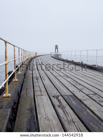 Whitby West Pier in thick fog - stock photo