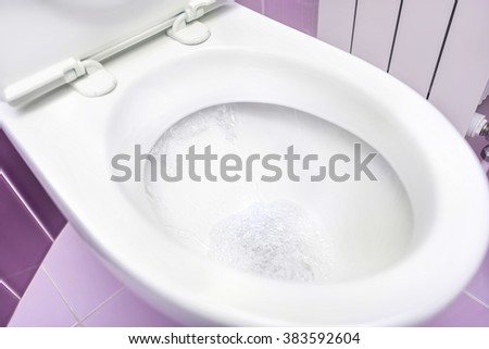 White a toilet bowl. Flowing water. Close-up. - stock photo