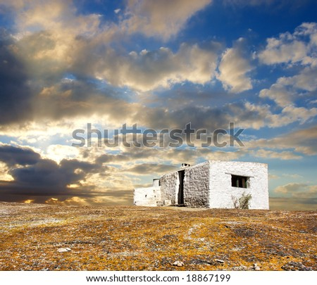 White abandoned house under dramatic sunset skies. Shot in West Coast Nature Reserve, near Langebaan, Western Cape; South Africa. - stock photo