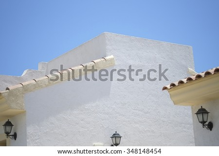 White Abstract Wall with blue sky and lamp and terracotta roof tiles
