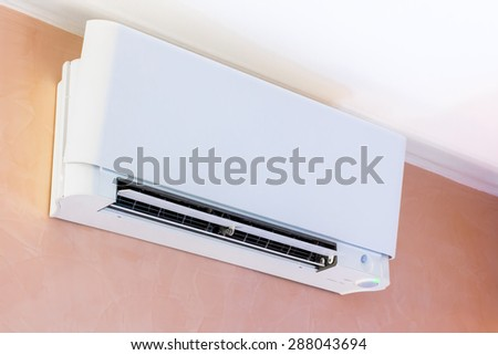white air conditioner installed on a pink wall - stock photo