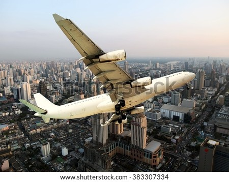 White aircraft flies over the city in sunset time. Under the aircraft wings visible buildings, skyscrapers and roads. - stock photo