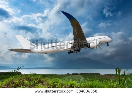 White aircraft is climbing in the blue sky. The plane flies over the lake, which shore overgrown with green grass. And the high mountain at the background. - stock photo