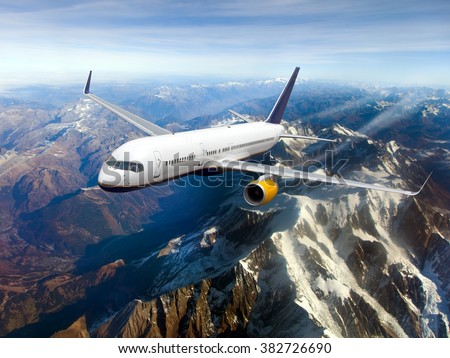 White aircraft with yellow Engines and blue Tail. The plane flies over snow-capped mountains. - stock photo