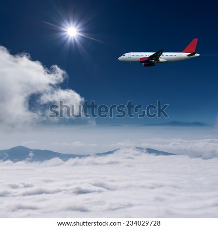 White airplane flying at high altitude above the clouds against the the sun - stock photo