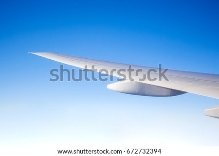 White airplane wing on the blue sky background