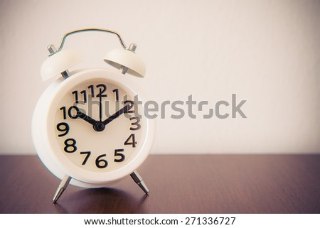 White alarm clock on table - retro effect style