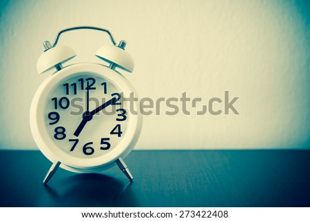 White alarm clock on table - retro effect style - stock photo