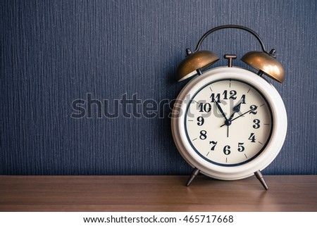 White alarm clock on wood table - Retro effect style
