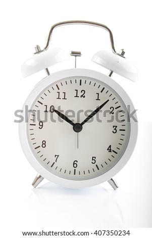 White alarm clock shows 7 after 10 - stock photo