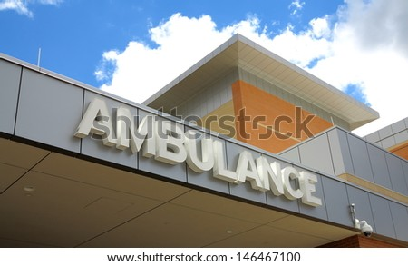 White ambulance sign on the side of a hospital - stock photo