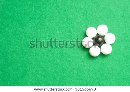White and black balls packed in the shape of a flower isolated on a green background
