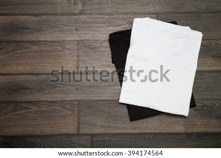 White and black blank t-shirt on wooden background - stock photo