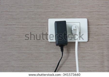 White and black cable plugged in a white electric outlet mounted on wall - stock photo