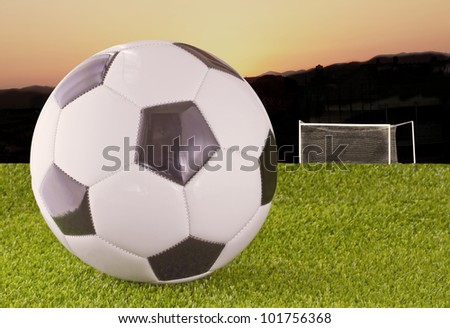 White and black football over grass, with goal and sunset on the back - stock photo