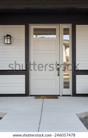 White And Black Front Entryway with White Siding, a White Front Door, and Black Framing